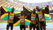 Team Jamaica pose with their national flags as they celebrate winning the men's 4x100 metres relay final during the IAAF World Athletics Championships at the Luzhniki stadium in Moscow